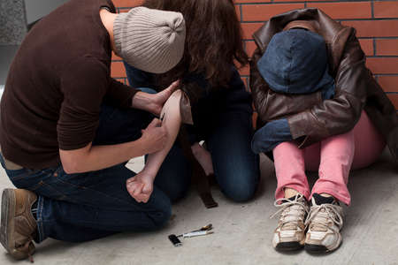 poorly: Three poorly dressed junkies by a brickwall mainlining  Stock Photo