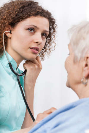 auscultate: Young nurse during examining elderly lady, vertical