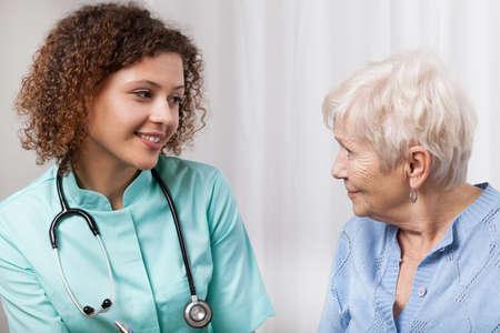 Pretty nurse during conversation with elderly patient Stock Photo