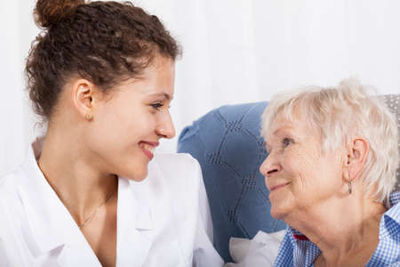Young nurse spending time with elderly lady photo