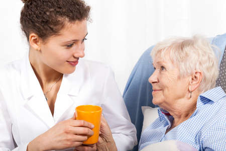 Nurse taking care of elderly woman, horizontal photo