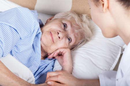 彼女の看護師とベッドに横たわっている病気の女性 写真素材