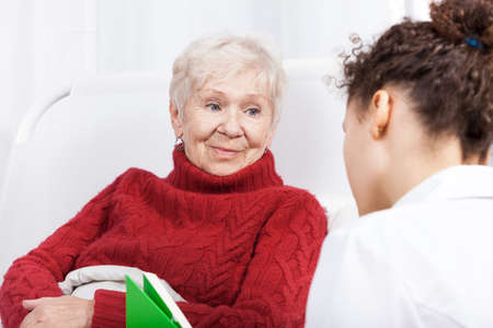 Elderly lady listening to reading nurse, horizontal photo
