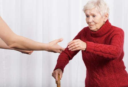osteoporosis: Anciana tratando de caminar con muletas