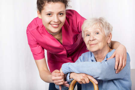 Young nurse with sitting elderly woman , horizontal photo