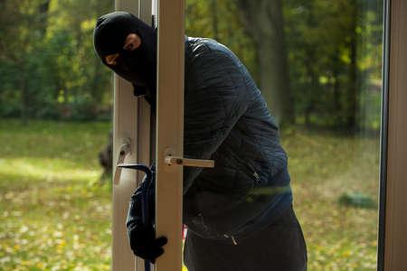 A masked burglar sneaking through the window photo