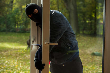 sneaking: A masked burglar sneaking through the window