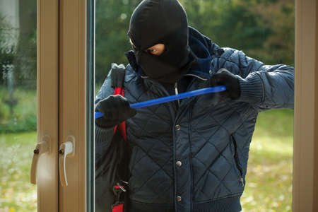 A burglar striving to open a window to a house