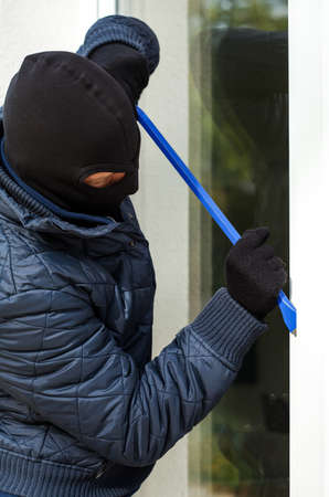 A masked burglar trying to open the window with a plastic stick photo