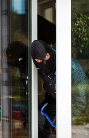 A masked burglar leaning out of the window photo