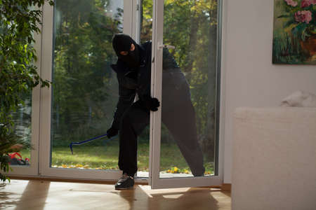 A burglar entering a house through a balcony window