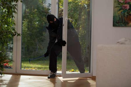 taking risks: A burglar entering a house through a balcony window