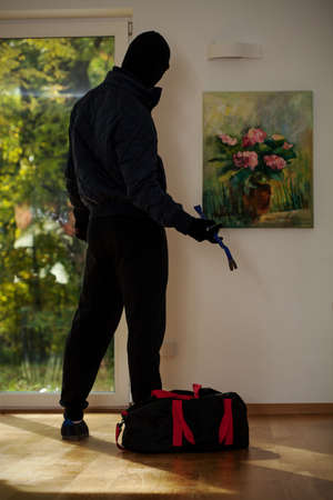 A standing burglar with a bag in front of a painting  photo