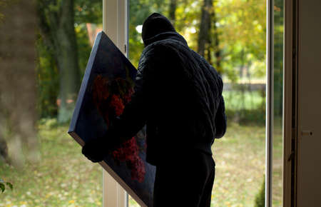 A thief holding a precious stolen painting photo