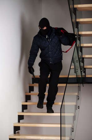 Bandit on stairs with a gun and bag with the loot photo
