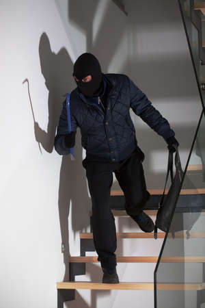 A masked burglar lying in wait for his victim on the stairs