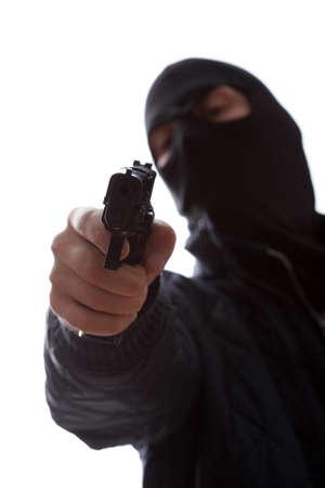 Dangerous murderer wearing a mask taking a target with a gun photo
