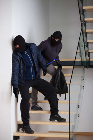 swindler: Two masked and armed criminals standing on the stairs