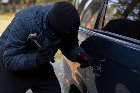 A masked burglar trying to break in a car using a hammer photo