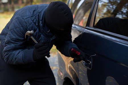 robo de autos: Un ladrón enmascarado tratando de entrar en un coche con un martillo Foto de archivo