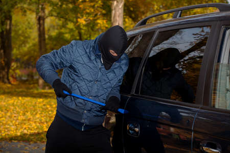 Bandit trying to open the cars door with a crowbar photo