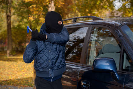 busted: A masked man robbing a car by breaking the window Stock Photo