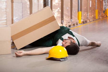 accidente trabajo: Joven trabajador masculino tendido en el suelo en almacén
