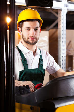 warehouseman: Young male forklift driver in yellow safety helmet Stock Photo