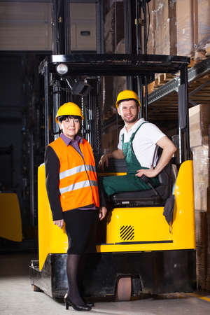 Female worker in vest and male worker in forklift at warehouse photo
