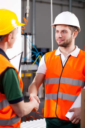 In factory male engineer and workman shake hands  photo