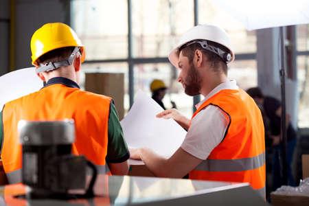 남성의 공장 노동자와 관리자는 계획을 분석하고