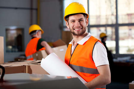 Smiling young factory worker is holding plans