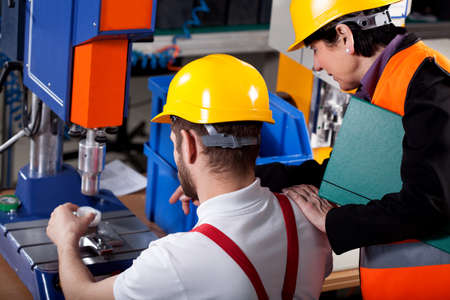 work workman: Female elder superior with young worker in warehouse Stock Photo