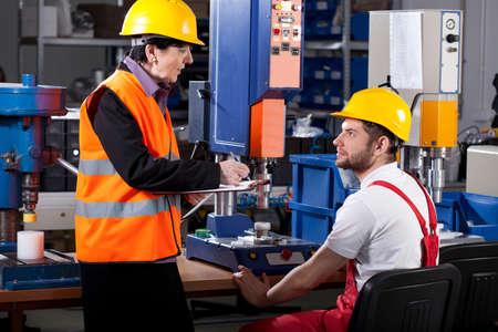 高齢者の女性上司は若い男性労働者を指示します。