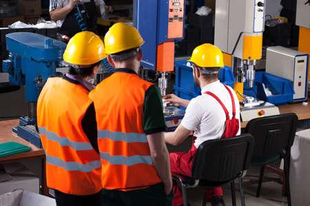 安全ヘルメットの 3 つの労働者が工場で働いています。 写真素材