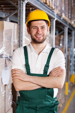 Smiling young male worker is standing in warehouse