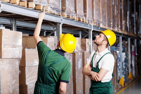 Two male workers next to boxes in warehouse Stock Photo