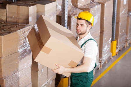 Young male worker is holding box in warehouse Stock fotó