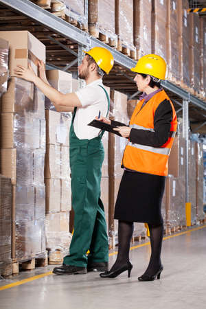 warehouseman: Elder female superior and young male worker in warehouse Stock Photo
