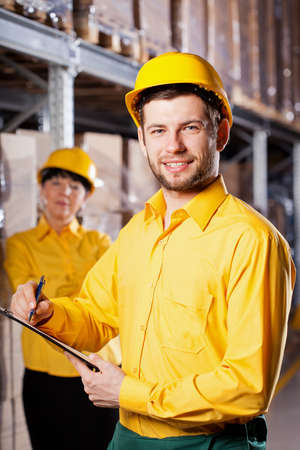 Young male worker in yellow uniform in warehouse photo