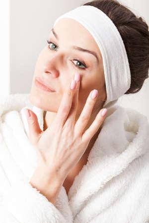 Young beautiful woman applying eye cream, vertical