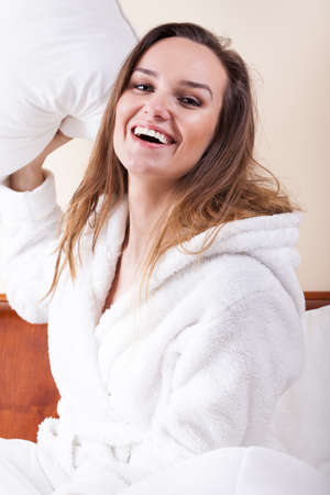 Happy woman in white bathrobe and pillow figh  photo