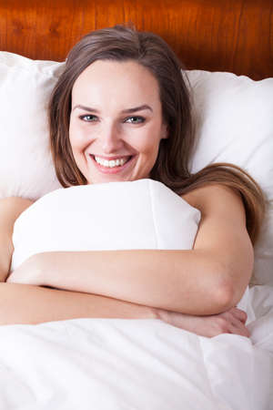 Happy woman in bed under white bedding