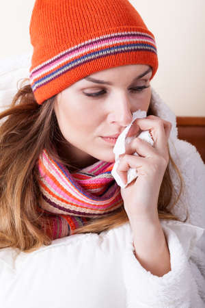 Sick woman in bed sneezing her nose Stock Photo - 27089842
