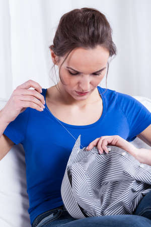 Young wife sewing a button to husbands shirt