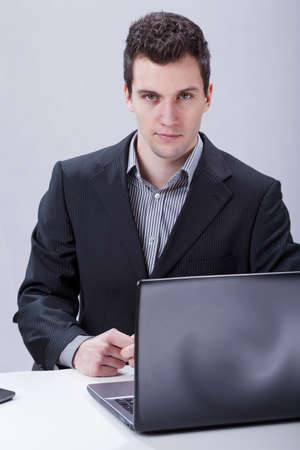 serious businessman: Serious businessman working on laptop at office