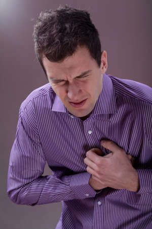 Young handsome man suffering from the chest pain photo