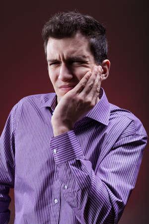 dent douleur: Jeune homme souffrant de graves maux de dents