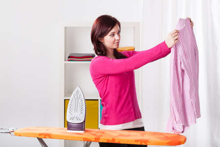 Young woman during ironing striped shirt, horizontal photo