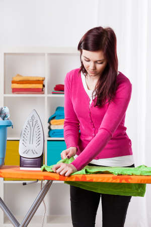 Young woman during ironing clothes at home photo